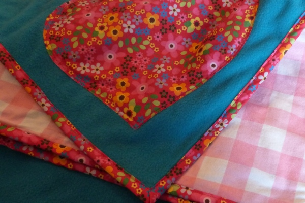 dog blanket in turquoise fleece with cerise floral trim